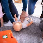 Specialist Giving Baby Cpr Dummy First Aid Training To His Colle
