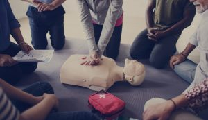 group of 5 people learning cpr from an instructor on a dummy